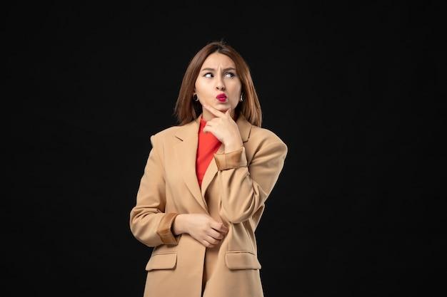 Vista dall'alto di una giovane donna sorpresa in un abito marrone chiaro che pensa profondamente a qualcosa al buio