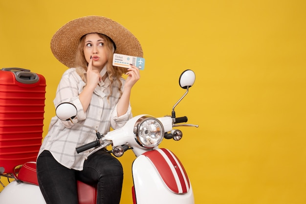 Top view of surprised young woman wearing hat and sitting on motorcycle and holding ticket on yellow