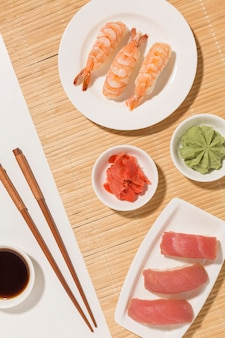 Top view sushi day concept with soy sauce and chopsticks