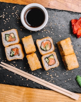 Top view sushi hot rolls with salmon and soy sauce