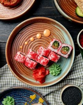 Vista dall'alto del rotolo di sushi con salmone avocado cetriolo e crema di formaggio ricoperto di caviale rosso con zenzero e wasabi su un piatto sul tavolo di legno