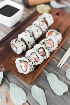 Top view of sushi roll on wooden tray with soya sauce and chopsticks