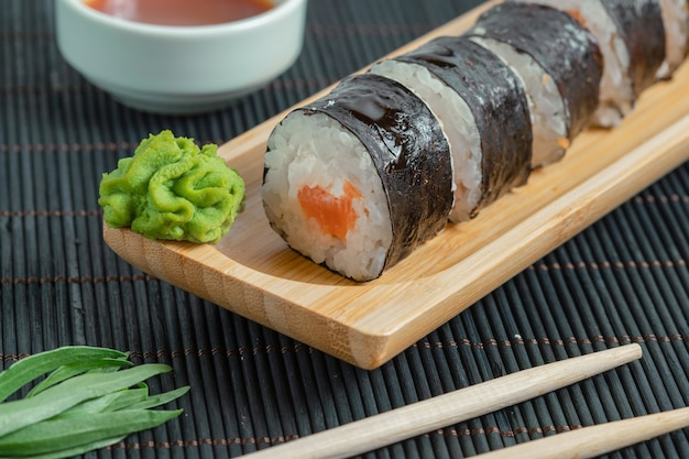 Top view of sushi rolls on black surface.