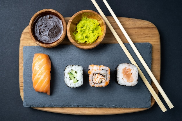 Top view of sushi rolls, maki, uramaki, nigiri and sashimi set served on stone slate.