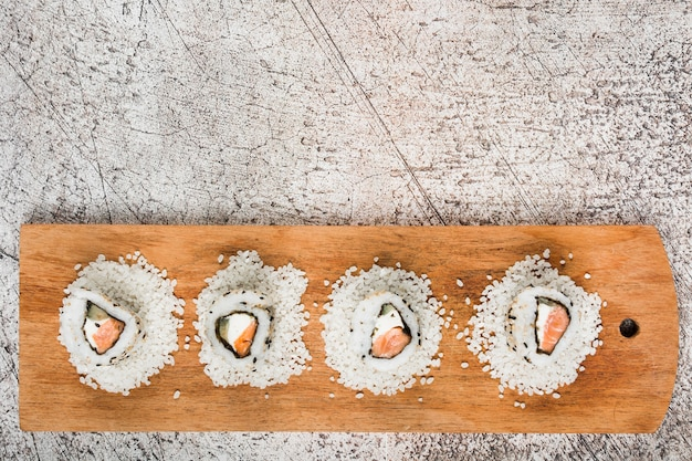 Top view of sushi rolls on white uncooked rice over the wooden tray against grunge background