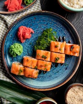 Vista dall'alto di involtini di sushi con avocado di anguilla di salmone e crema di formaggio su un piatto con zenzero e wasabi