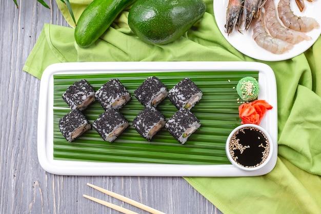 Rotoli di sushi di vista superiore con i gamberi con wasabi allo zenzero e salsa di soia su un piatto
