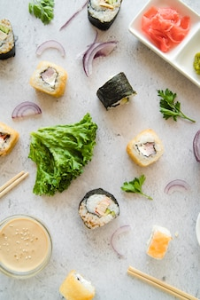 Top view sushi rolls with spices and ingredients
