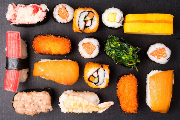 Top view of sushi set on black background, japanese food.
