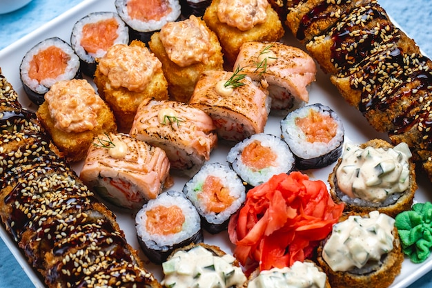 トップビュー寿司セット照り焼きソースとゴマフィラデルフィアウィットサーモン酒巻きわさびと生姜のボード上のホット寿司ロール