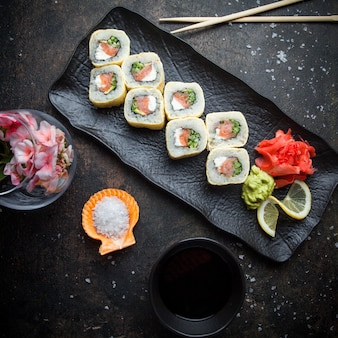 Top view sushi set with pickled ginger and wasabi and soy sauce and chopsticks in dark plate