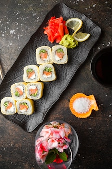Top view sushi set with pickled ginger and wasabi and soy sauce in dark plate