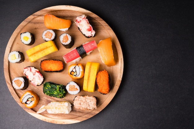 Top view of sushi set on wooden plate on black background, japanese food.