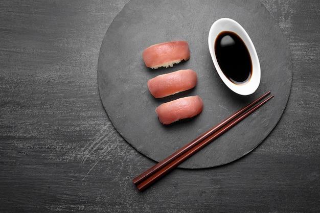 Вид сверху суши с палочками и соусом