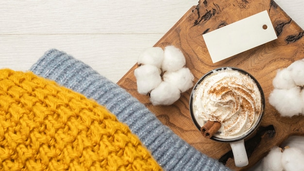 Top view of sweater with cotton and cup of coffee with whipped cream