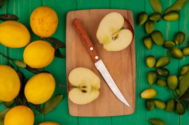 Vista dall'alto di mele dolci su una tavola da cucina in legno con coltello con kinkan verdi e limoni gialli isolati su una parete di legno verde