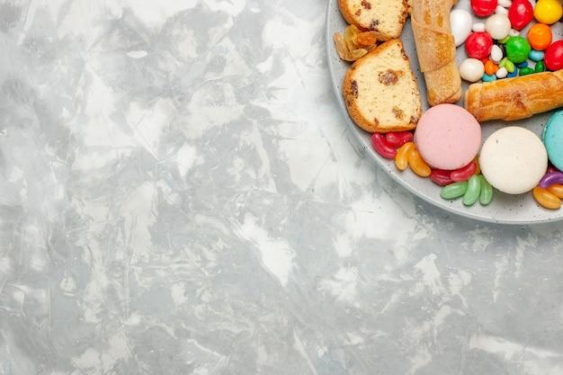 Vista dall'alto di bagel dolci con fette di torta macarons e caramelle sulla superficie bianca