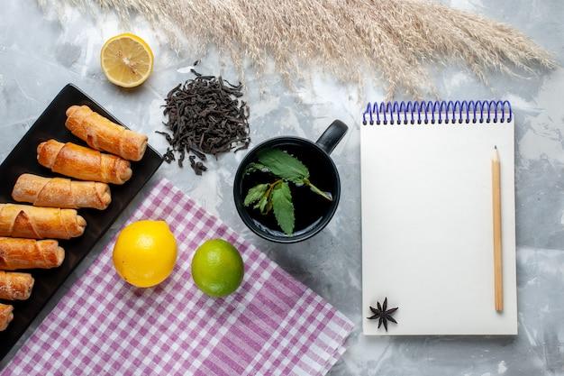ライトテーブルのレモンティーのメモ帳と一緒に上面の甘い腕輪、甘いペストリーケーキ、砂糖茶を焼く