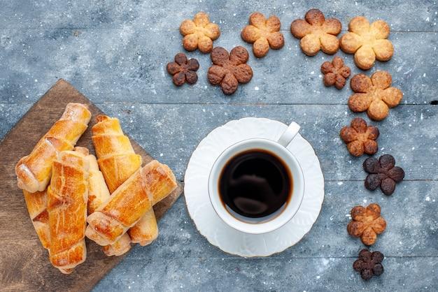 Vista dall'alto braccialetti dolci con i biscotti e la tazza di caffè sul biscotto di zucchero della torta della torta della pasticceria del forno dolce della tavola grigia
