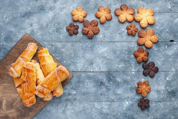 회색 배경에 쿠키와 상위 뷰 달콤한 팔찌 달콤한 빵 과자 케이크 설탕 비스킷