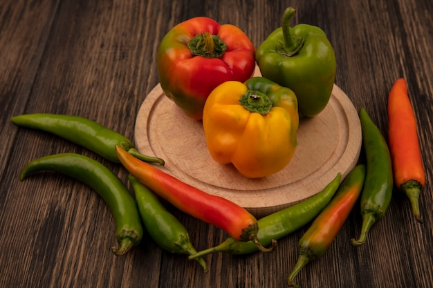 Top view of sweet bell shaped peppers on a wooden kitchen board with long shaped peppers isolated on a wooden surface