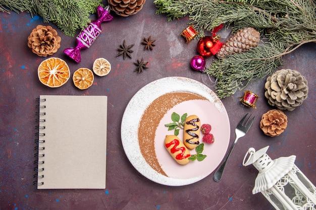Vista dall'alto di biscotti dolci all'interno del piatto con blocco note su nero