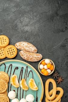 灰色の背景にキャンディーとクッキーと甘いビスケットの上面図
