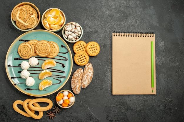 Vista dall'alto biscotti dolci con caramelle e biscotti su sfondo grigio