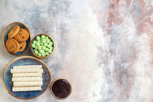 Вид сверху сладкое печенье с конфетами на светлом фоне фото чайный десерт