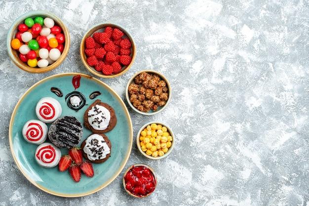 흰색 책상 사탕 설탕 비스킷 케이크 달콤한 차에 초콜릿 케이크와 사탕과 상위 뷰 달콤한 비스킷