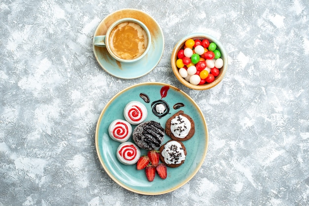 上面図チョコレートケーキと白い背景の上のコーヒーと甘いビスケットキャンディシュガービスケットケーキ甘いお茶