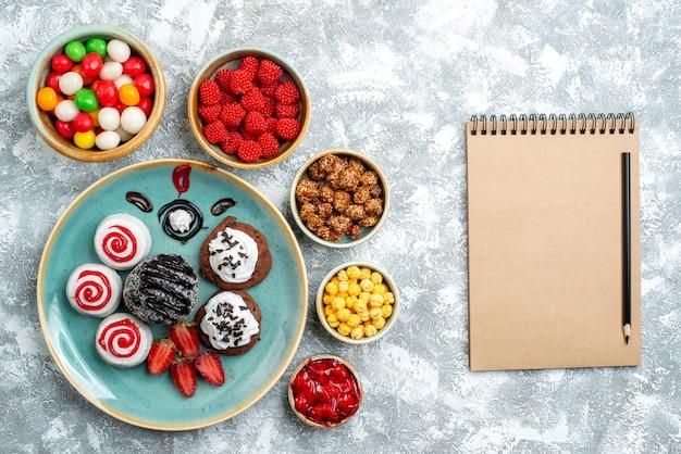 Vista dall'alto biscotti dolci con torta al cioccolato e caramelle su sfondo bianco chiaro zucchero candito torta biscotto tè dolce