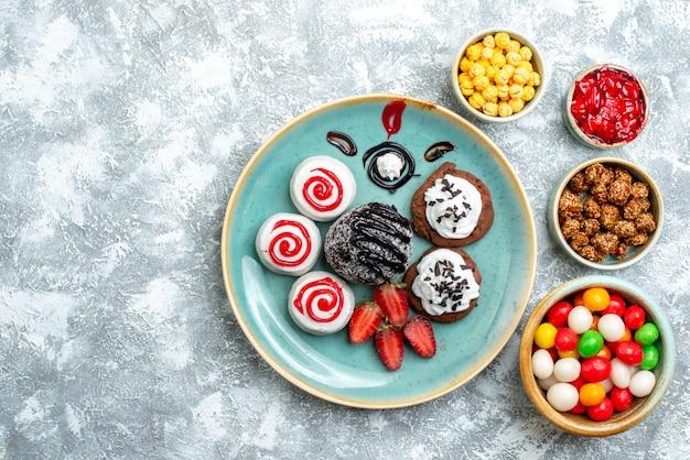 Vista dall'alto biscotti dolci con torta al cioccolato e caramelle su sfondo bianco zucchero candito torta biscotto tè dolce