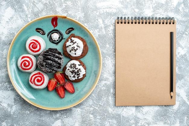 上面図白い背景の上のチョコレートケーキと甘いビスケットキャンディシュガービスケットケーキ甘いお茶