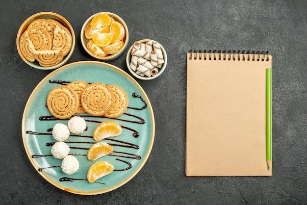 灰色の背景にココナッツキャンディーとトップビューの甘いビスケット