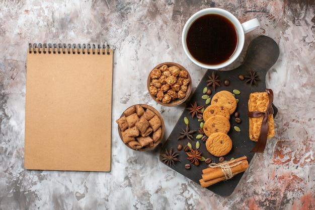 Вид сверху сладкого печенья с кофе и грецкими орехами на светлом столе цвета торта