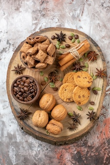 Top view sweet biscuits with coffee and walnuts on light table