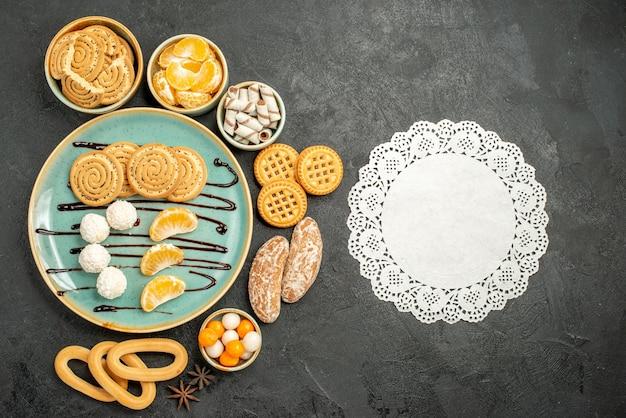 灰色の背景にクッキーとキャンディーと甘いビスケットの上面図