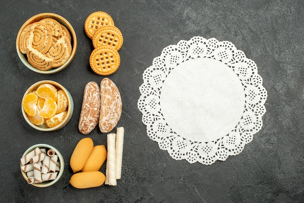 Top view sweet biscuits with cookies and fruits on grey background