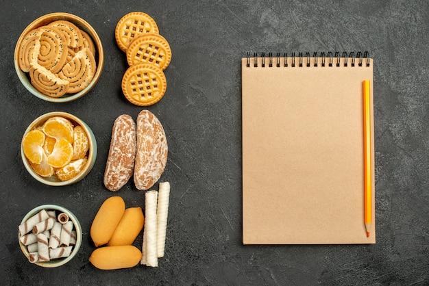 Vista dall'alto biscotti dolci con biscotti e frutta su una scrivania grigia