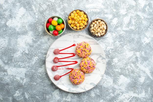 上面図白い背景の上のクリームと甘いビスケットクッキービスケットシュガーパイケーキスウィートティー