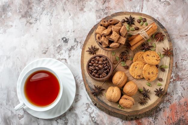 Вид сверху сладкого печенья с чашкой чая и грецкими орехами на светлом столе