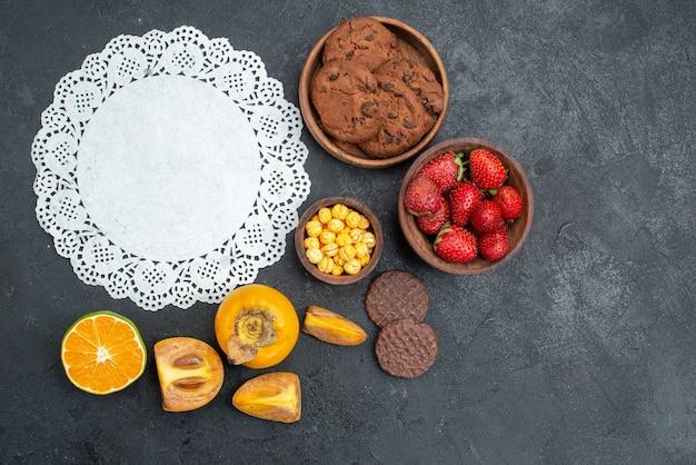 暗いテーブルの甘いクッキーにフルーツとトップビューの甘いビスケット