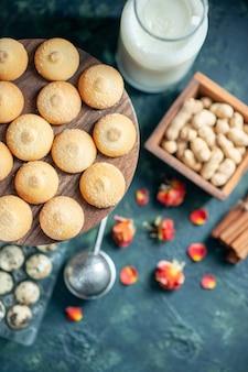 ダークブルーの背景にミルクと甘いビスケットの上面図パイビスケットティーデザートクッキーシュガーケーキ