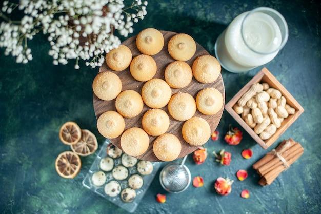 ダークブルーの背景にナッツとミルクの甘いビスケットの上面図パイビスケットティーデザートクッキーシュガーケーキ