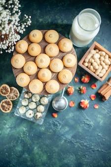 Vista dall'alto biscotti dolci con noci e latte su sfondo blu scuro torta biscotto tè biscotto torta di zucchero