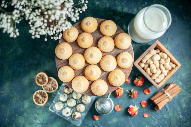 Top view sweet biscuits with nuts and milk on dark blue background pie biscuit tea dessert cookie sugar cake