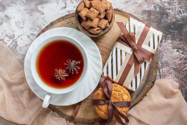 Вид сверху сладкое печенье с подарком и чашкой чая на светлом столе