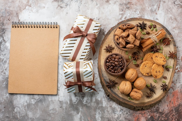 Вид сверху сладкое печенье с подарками и грецкими орехами на светлом столе