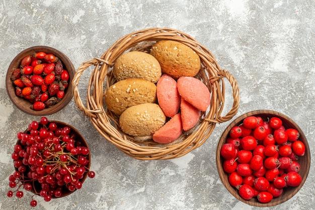 上面図白い背景に赤い果物と甘いビスケット